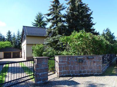 Grundstückseinfahrt mit Granitsteinmauer und Tor