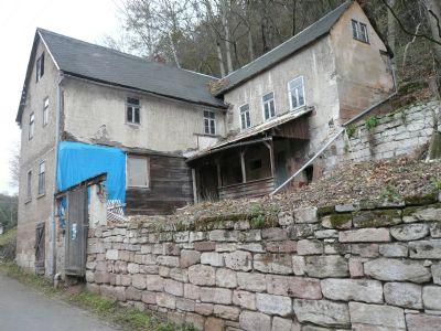Verputztes Fachwerkhaus mit Sandsteinsockel am Hang