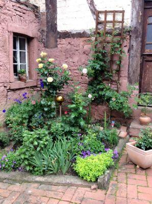 Liebevoll gestaltete Blumenbeete im Innenhof